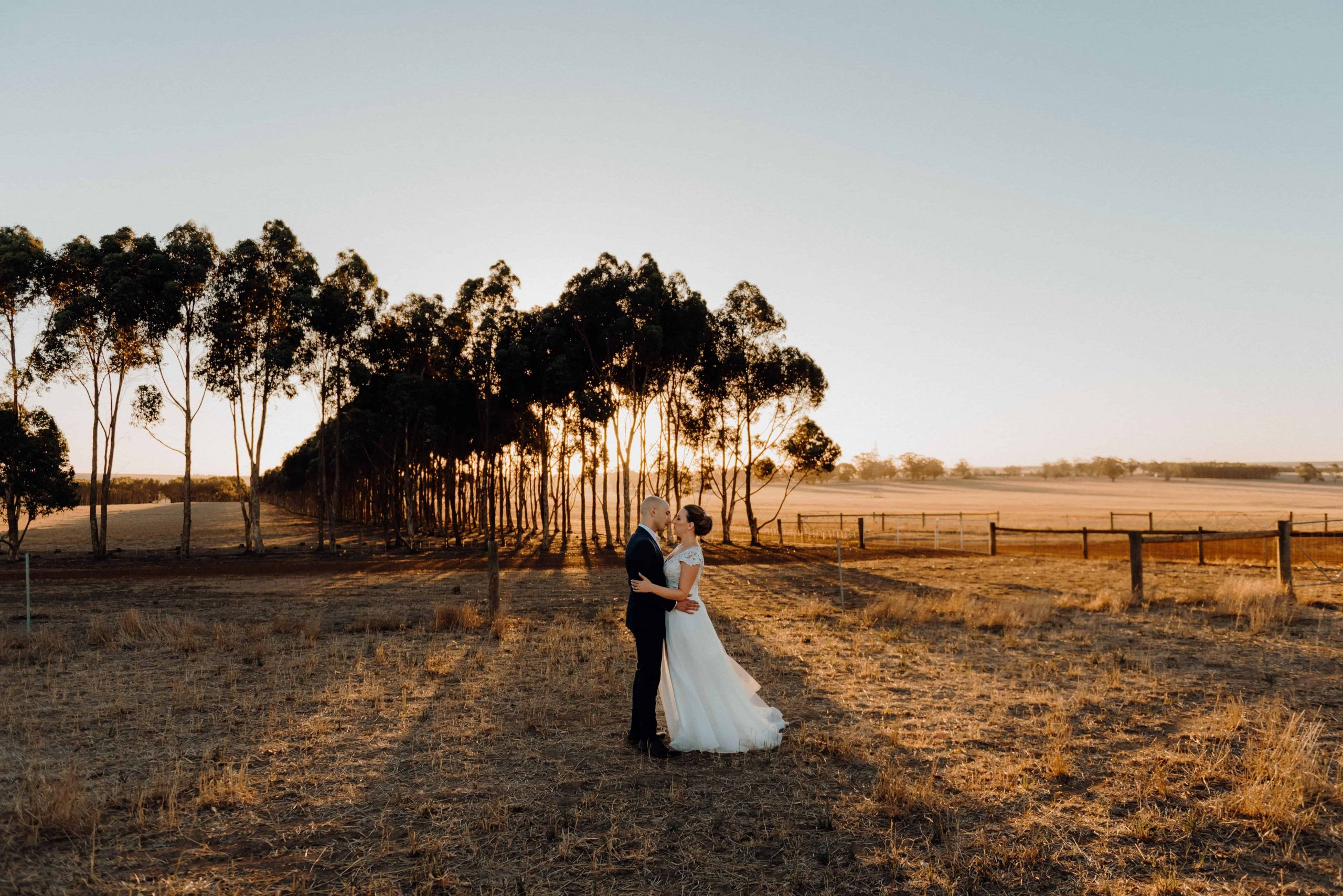 bride and groom standing together in an open field at sunset on a rural farm